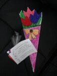 Na zdjęciu znajdują się kolorowe kartki zdobione kwiatami z bibuły z życzeniami z okazji Dnia Babci i Dziadka