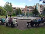 na zdjęciu mieszkańcy siedzący na ławeczkach przy naszej fontannie
