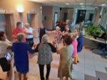 Na zdjęciu taniec w kółeczku uczestników zabawy